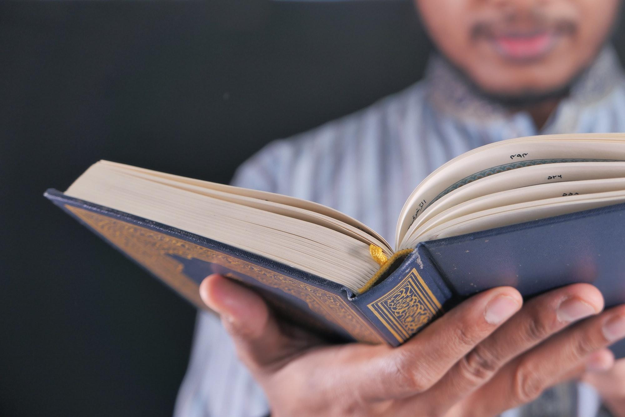 Muslim mans reading quran at night